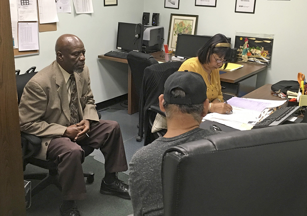 Nathan Singletary, 67, a social worker for 40 years, listens as Employment Specialist Luz Rivera, 68, interviews program participant Luis Quinones, 66, at the AARP Foundation in Harrisburg, Pa.