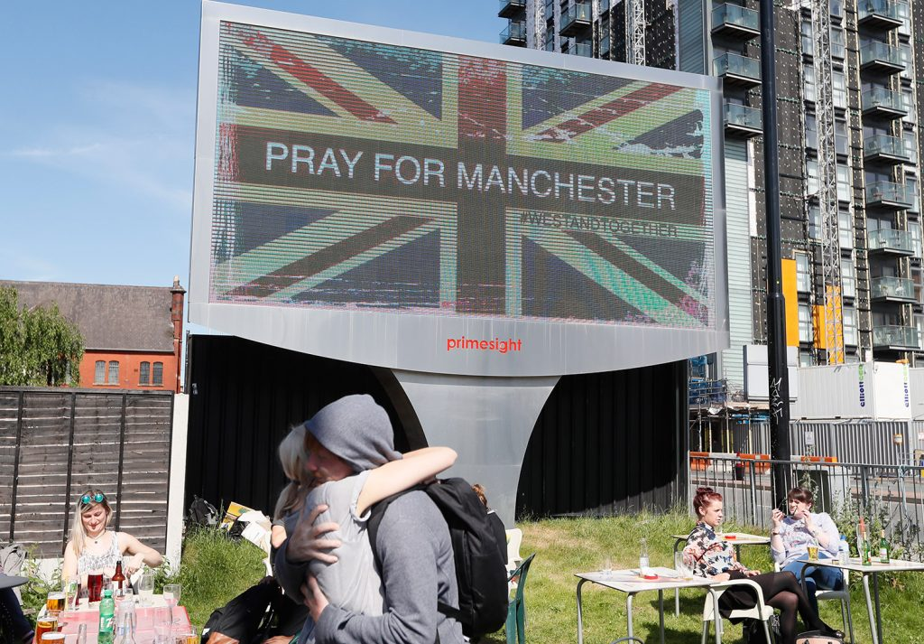 A couple embrace under a billboard in Manchester city center on Tuesday, the day after the suicide attack at an Ariana Grande concert that left at least 22 people dead.