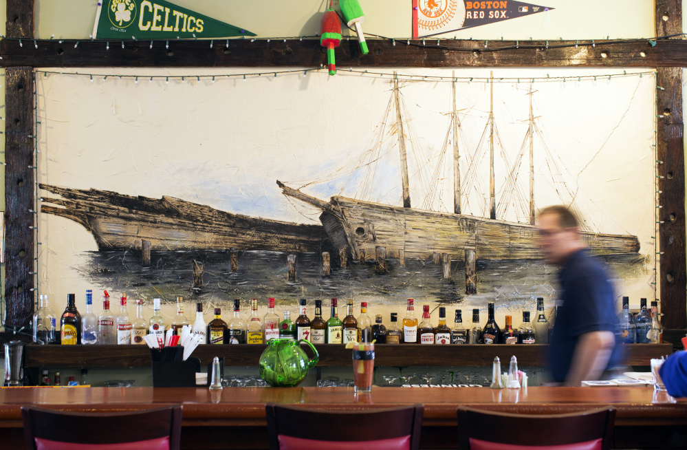 A mural of schooners Hesper and Little Luther is framed with wood from the ships after they were dismantled. It hangs behind the bar at the Twin Schooner Pub, which is tended by Greg McAllister.