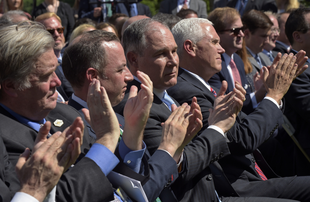 Administration officials, from left, White House chief strategist Steve Bannon, Chief of Staff Reince Priebus, Environmental Protection Agency Administrator Scott Pruitt, and Vice President Mike Pence, applaud as President Trump announces that the U.S. will withdraw from the Paris climate change accord as he speaks in the Rose Garden of the White House on Thursday.