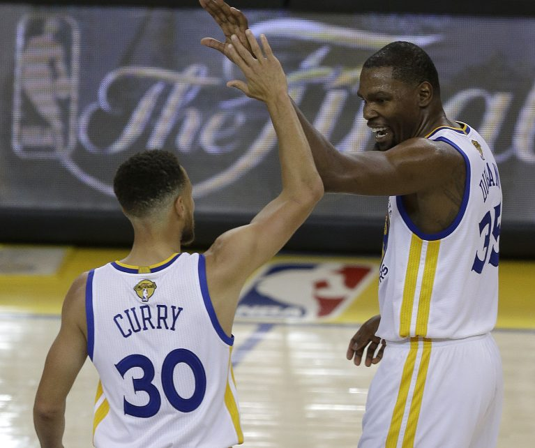 Golden State guard Stephen Curry and forward Kevin Durant react after scoring against the Cleveland Cavaliers in the first half of Game 1 of NBA Finals Thursday night in Oakland, Calif.