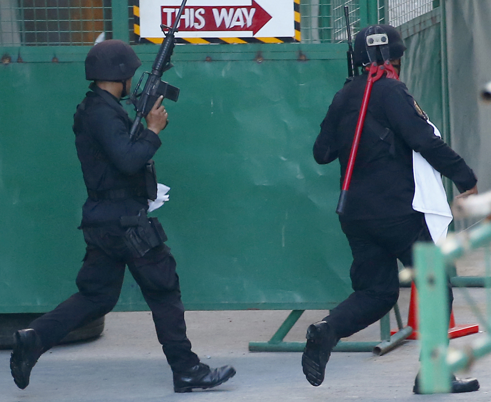 Police rush toward the entrance to the Resorts World Manila complex after a masked gunman stormed the hotel-casino.