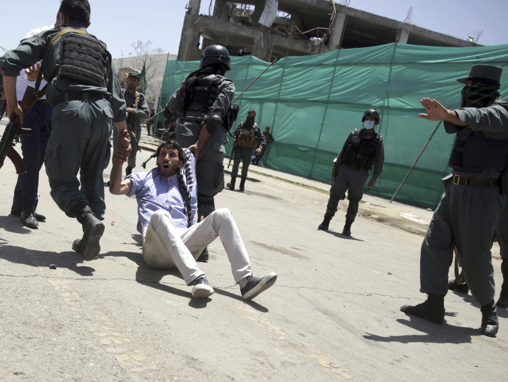 Police arrest a protester during a demonstration in Kabul, Afghanistan, Friday. Hundreds of demonstrators demanded better security in the Afghan capital in the wake of a powerful truck bomb attack that killed 90 people.