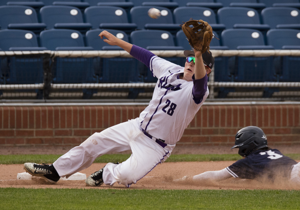 Deering third baseman Alex McGonagle dives off the base Friday to catch an off-the-mark throw as Ben Stasium of Portland slides safely with a steal. Deering had to play two games at Hadlock Field – losing both – to complete a weather-hampered baseball schedule.