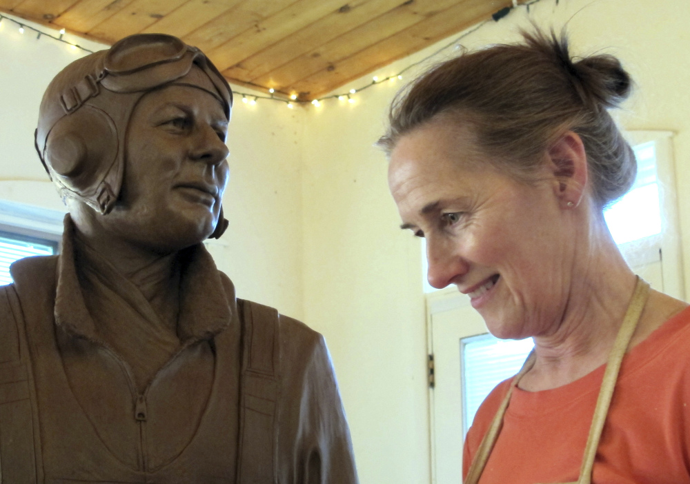 Sculptor Susan Geissler works on a clay likeness of World War II hero C. Wade McClusky Jr. in her Youngstown, N.Y., studio. The model will form the basis for a bronze monument in McClusky's honor.