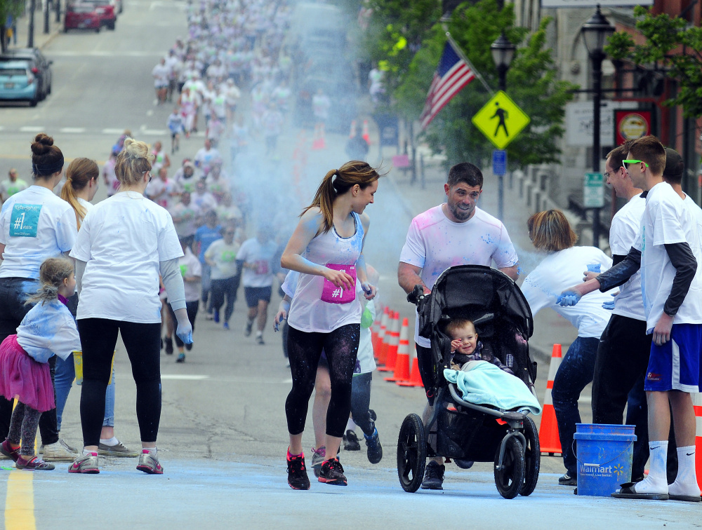 Kristin and Josh DuBois and their son Ethan, of Belgrade, continue their run Saturday after passing through blue powder at the first color station on Water Street during a 5K Color Dash race in Augusta.