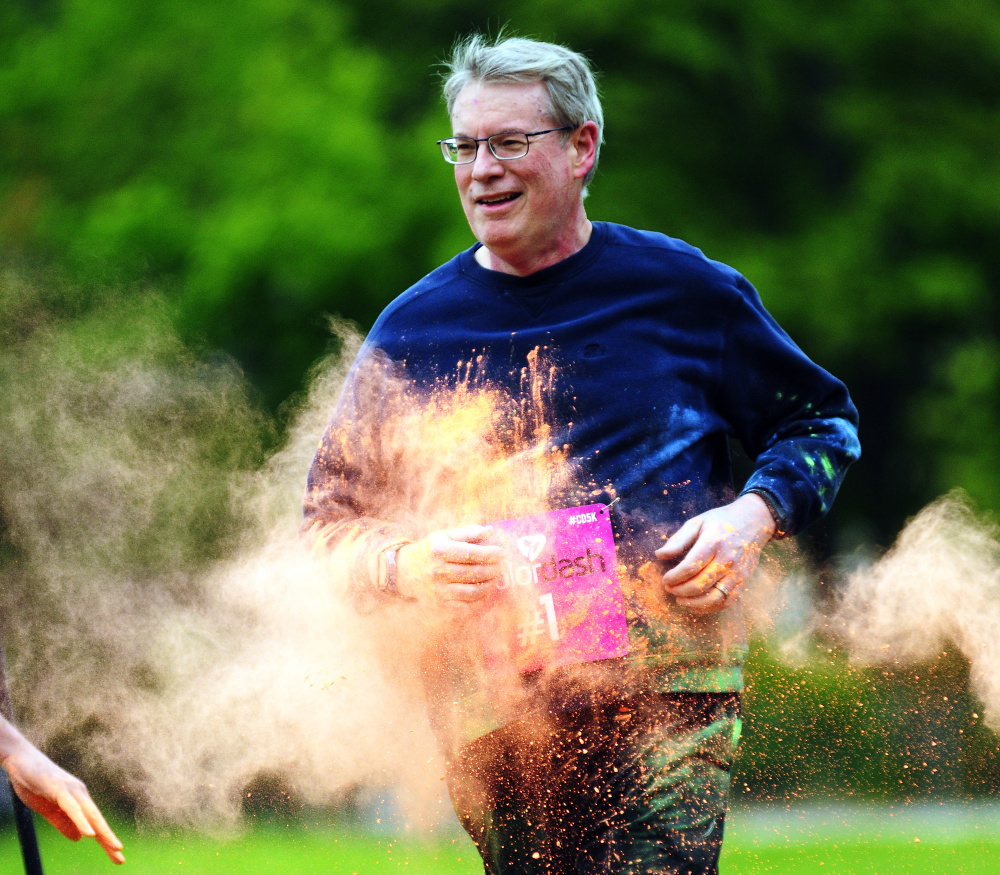 A runner's hit with orange powder Saturday at the Kennebec Valley YMCA during a 5K Color Dash race in Augusta.