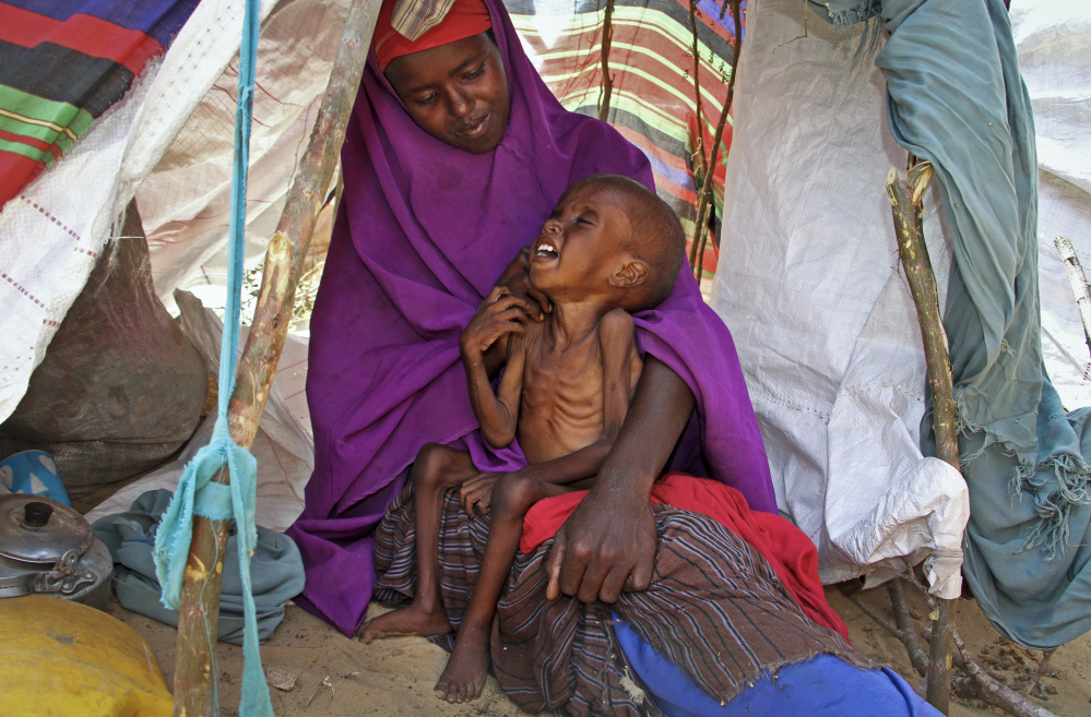 A newly displaced Somali mother comforts her malnourished child in their makeshift shelter at a camp in the Garasbaley area on the outskirts of Mogadishu, Somalia.