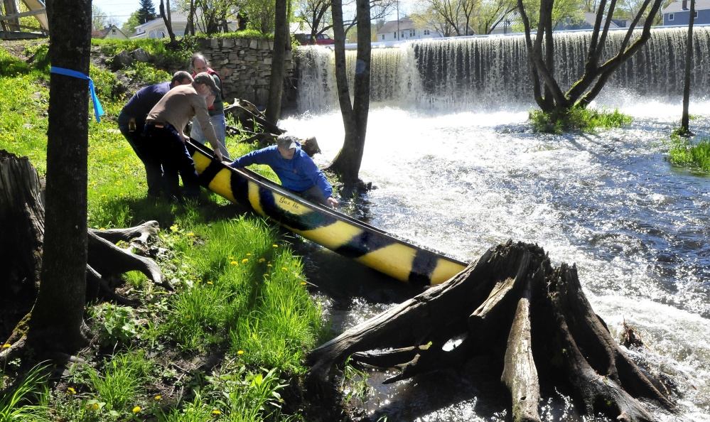 Men remove a canoe below the dam on Outlet Stream in Vassalboro on May 16, the day after Mollie Egold of Vassalboro and her son William, 5, went over the dam and he was thrown from the canoe. William was pulled from the water but died in the hospital of severe hypothermia.