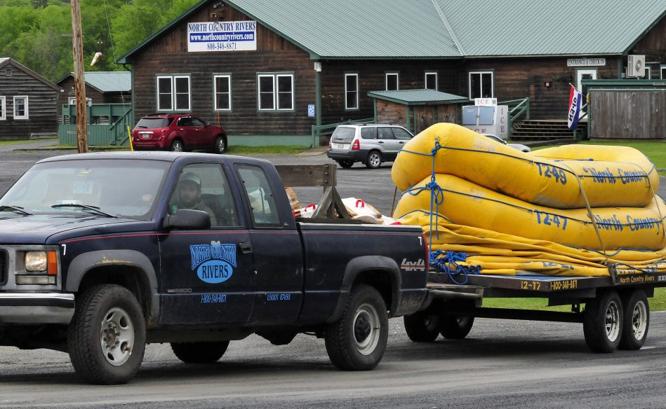 A North Country Rivers employee hauls a trailer full of white water rafts while leaving the base lodge of the company in Bingham on Monday. The Maine Warden Service continues to investigate the death of Richard Sanders on Saturday after the raft he was in flipped over on the Dead River.