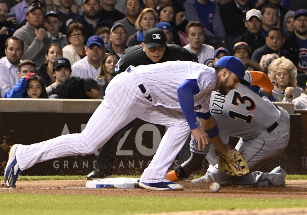 Miami's Marcell Ozuna slides safely into third base as Cubs third baseman Kris Bryant, left, takes a late throw during the seventh inning of Chicago's 3-1 win Monday night at Wrigley Field in Chicago. Bryant hit a two-run home run, his 13th, in the first inning.
