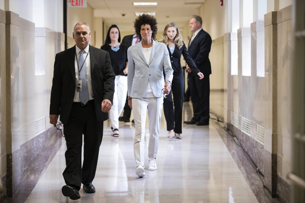 Andrea Constand, center, walks to the courtroom during Bill Cosby's sexual assault trial at the Montgomery County Courthouse in Norristown, Pa., on Tuesday. Cosby is accused of drugging and sexually assaulting Constand at his home outside Philadelphia in 2004.