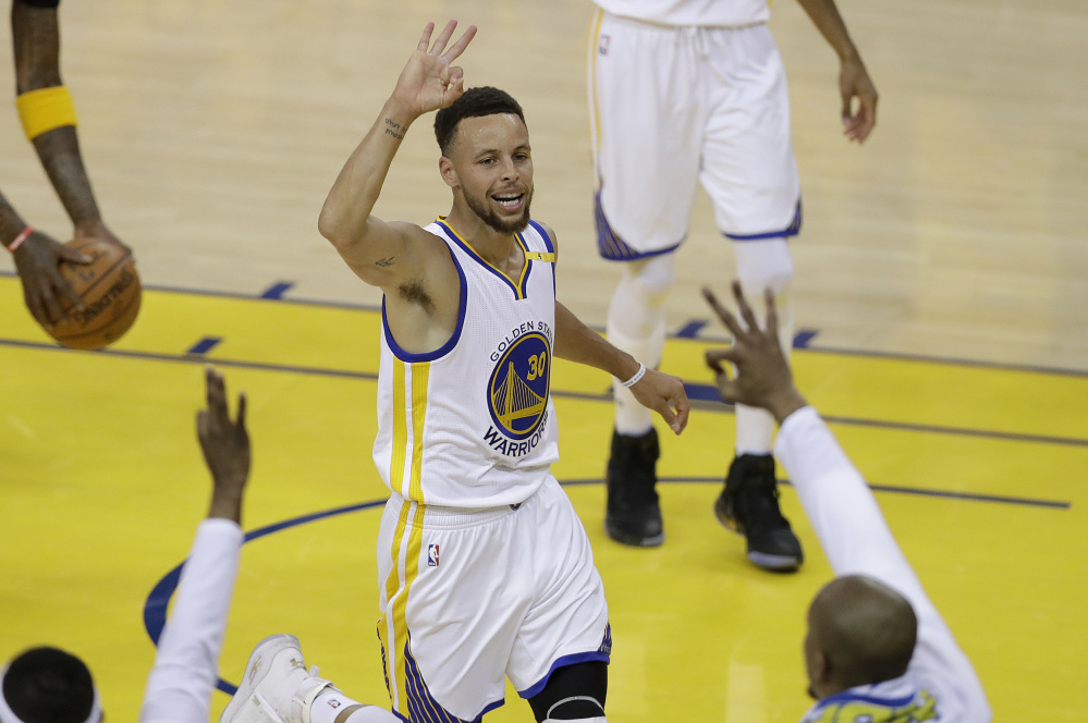 Golden State guard Stephen Curry gestures after scoring against Cleveland during Game 2 of the NBA Finals on Sunday in Oakland. The Warriors made a finals record 18 3-pointers in a blowout victory.