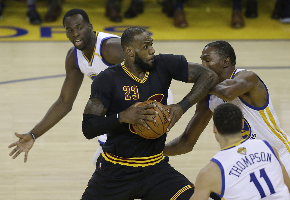 Cleveland Cavaliers forward LeBron James (23) shoots between Golden State Warriors forward Draymond Green, top, guard Klay Thompson (11) and forward Kevin Durant during the first half of Game 2 of basketball's NBA Finals in Oakland, Calif., on Sunday.