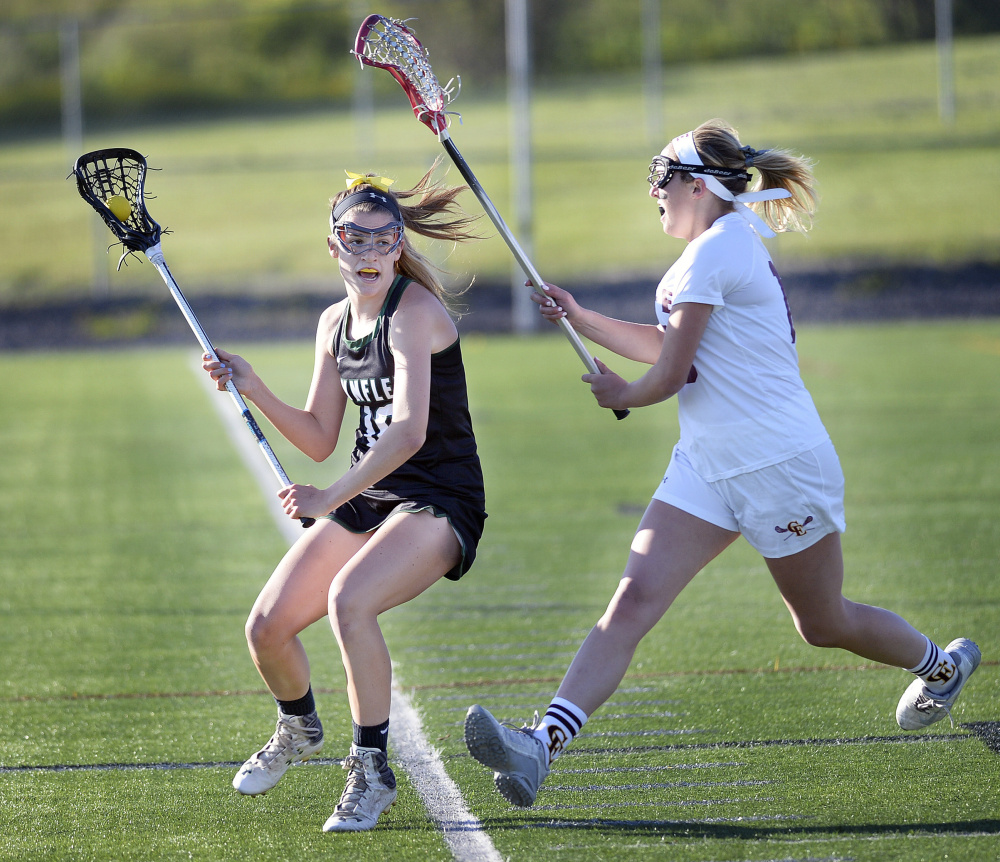 LZ Olney of Waynflete looks for an open teammate as Caroline Coburn of Cape Elizabeth pursues Wednesday night during the Capers' 10-6 victory in a Class B South girls' lacrosse quarterfinal. Cape will be at top-ranked Kennebunk in a semifinal Saturday.