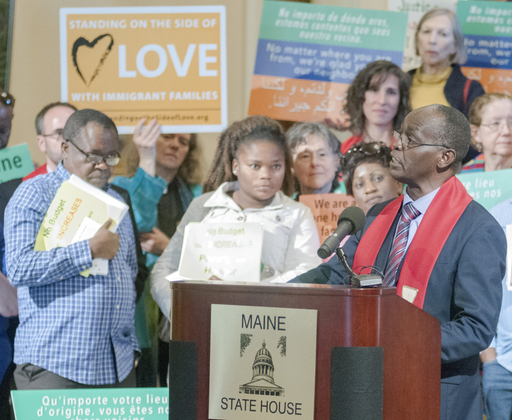 Staff photo by Joe Phelan The Rev. Nathan Ndayiziga speaks Wednesday at a rally about immigration led by religious leaders in the State House Hall of Flags in Augusta.