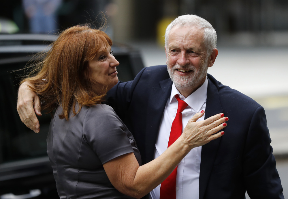 Britain's Labour party leader Jeremy Corbyn is greeted as he arrives at Labour party headquarters in London on Friday, the day after national elections that gave Labour more seats in Parliament.