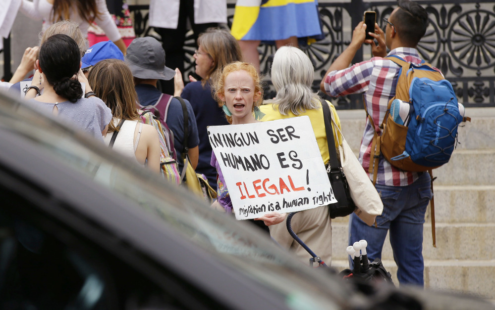 "Associated Press/Stephan Savoia Bostonian Anna Hadingham's sign translates as ""No Human Is Illegal"" during a Sanctuary State Rally outside the Massachusetts Statehouse Friday in Boston. Inside the building, a sanctuary bill was discussed."
