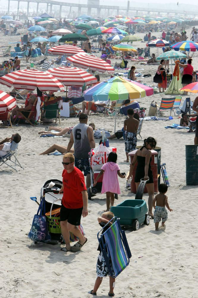 ** ADVANCE FOR MONDAY, JULY 23 ** People walk on a crowded beach in Ocean City, N.J., Tuesday, July 17, 2007. That time-honored New Jersey tradition of sneaking onto the beach without paying could get much harder soon in this south Jersey community, which is considering eliminating beach badges and issuing electronic bracelets to paying customers. That would enable authorities to wirelessly