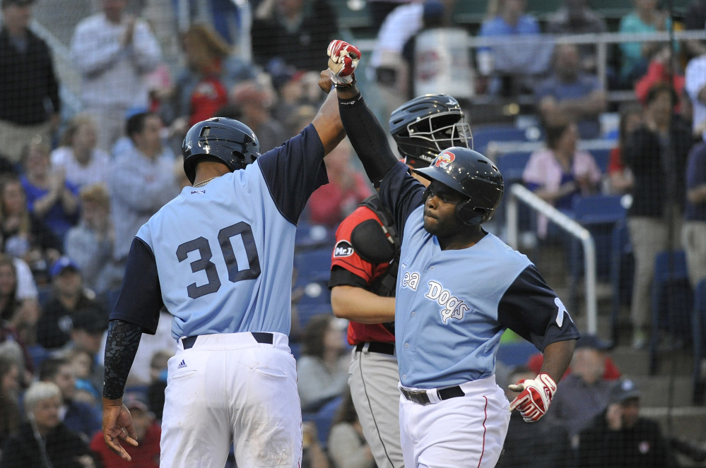 Josh Tobias, right, is greeted at home plate by teammate Jeremy Barfield after Tobias' three-run home run against the Erie SeaWolves on Friday at Hadlock Field. Portland won 7-5 on Nick Longhi's two-run home run with two outs in the bottom of the ninth.