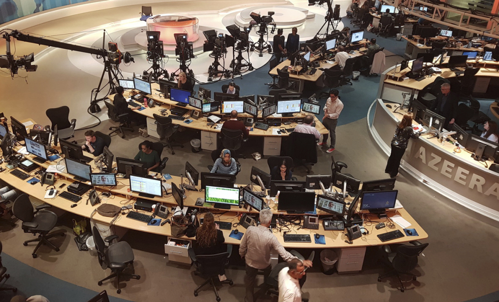 Al-Jazeera staff work at their TV station in Doha, Qatar, on Thursday. Critics allege that the news network that is widely seen on Arab channels worldwide is promoting Islamist movements as a tool of Qatar's foreign policy.