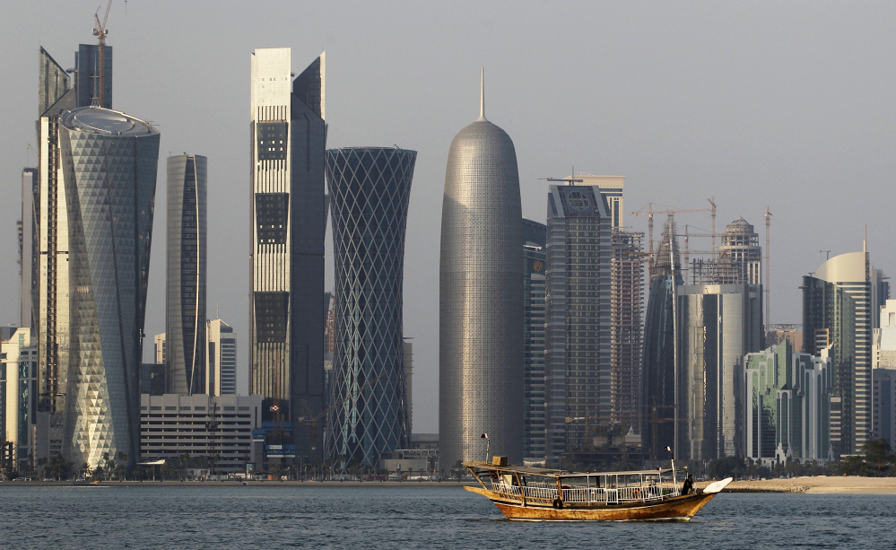 A traditional dhow floating in the Corniche Bay of Doha, Qatar, contrasts with tall buildings of the financial district. Qatar is facing a diplomatic crisis with other Arab nations.