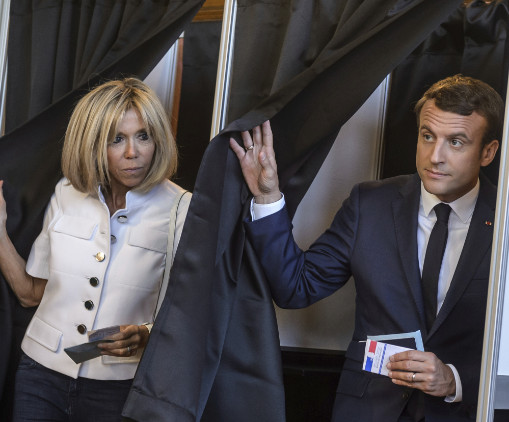 French President Emmanuel Macron and his wife, Brigitte, leave a polling booth after voting in the first round of the two-stage legislative elections in Le Touquet, France, on Sunday.