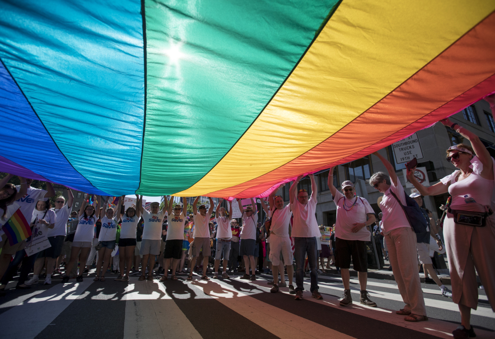 Marchers unfurl a huge rainbow flag as they prepare to march in the Equality March for Unity and Pride in Washington on Sunday. Thousands paraded past the White House.