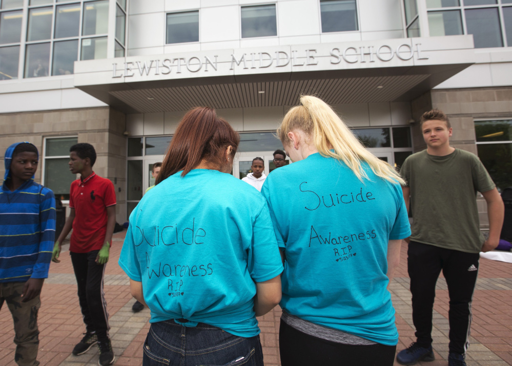 """Lewiston Middle School students wear """"Suicide Awareness"""" shirts outside the school after the suicide of seventh-grader Anie Graham. Superintendent Bill Webster says students are still visiting the extra counselors put in place at the school in the wake of Anie's death."""
