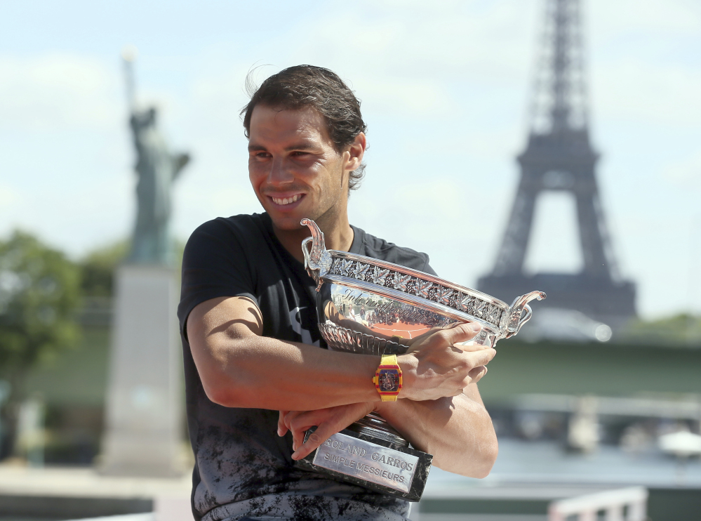 Spain's Rafael Nadal poses for photos with his French Open trophy aboard a barge cruising on the Seine river in Paris on Monday.