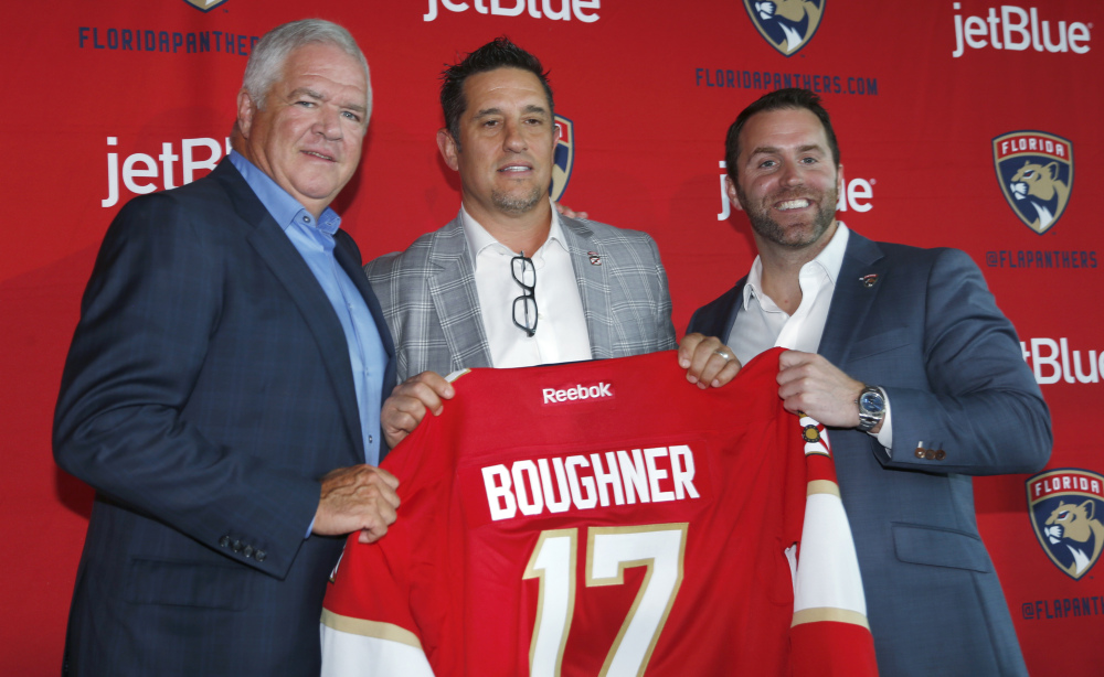 Bob Boughner, center, poses with Dale Tallon, Florida Panthers president of hockey operations, and Matthew Caldwell, president and CEO, after being named coach.