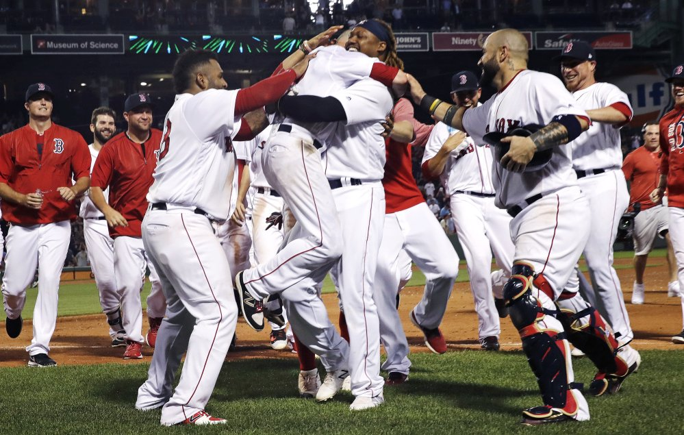Dustin Pedroia is lifted by Hanley Ramirez after his game-winning RBI single in the 11th inning of Monday night's game against the Philadelphia Phillies.