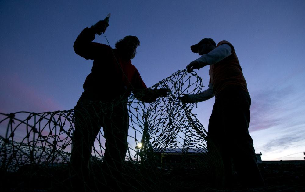 Fishermen mend groundfishing nets in Portland in this 2013 photo. Congress is considering a bill that would make competitive grants available to support new and established training, education and technical programs for young fishermen.