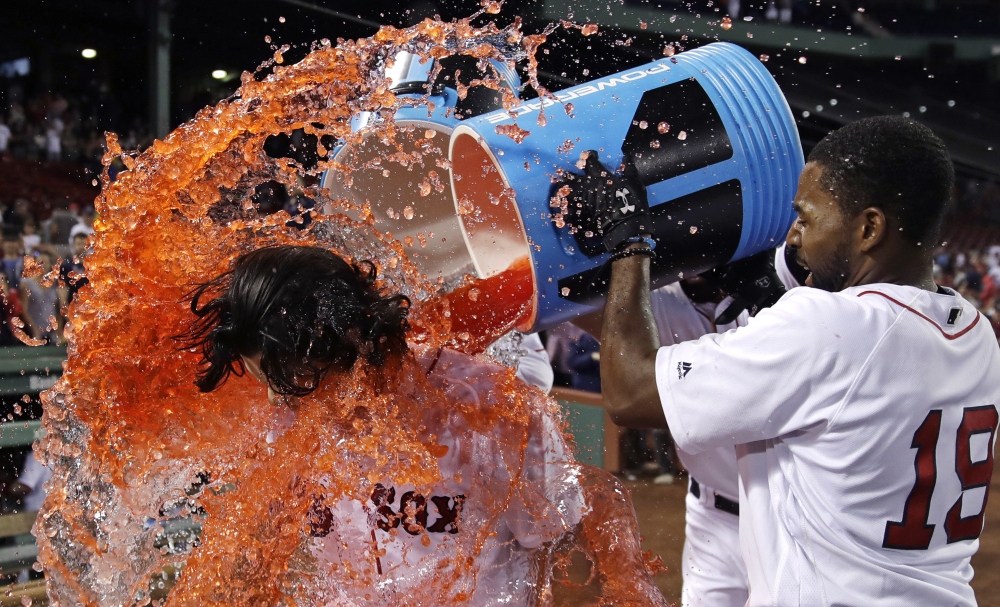Boston's Andrew Benintendi is doused by Jackie Bradley Jr. and others after his game-winning RBI single in the bottom of the 12th inning against the Philadelphia Phillies at Fenway Park on Tuesday. The Red Sox won 4-3.