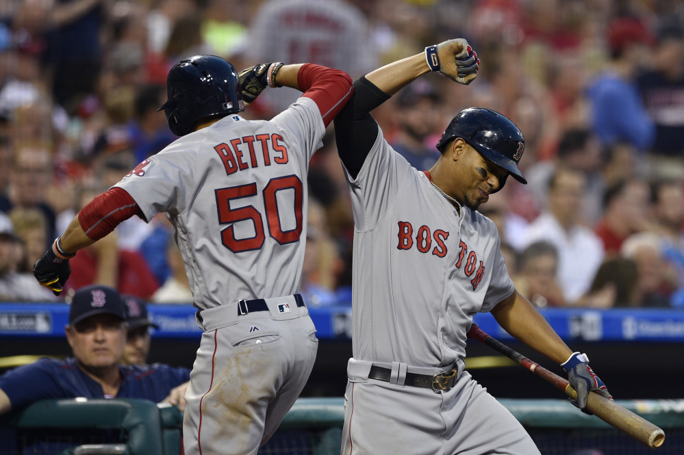 Boston's Mookie Betts celebrates with Xander Bogaerts after Betts hit a solo home run off Philadelphia's Jeremy Hellickson in the fourth inning Wednesday night in Philadelphia.