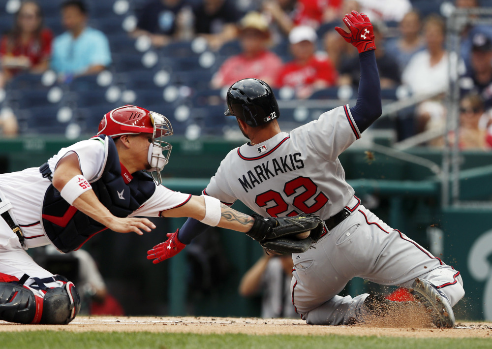 Nick Markakis of the Braves slides safely into home on a single by Matt Adams as Nationals catcher Jose Lobaton reaches with a late tag during the first inning of Atlanta's 13-2 win Wednesday.