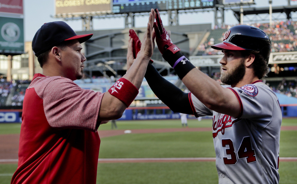 Bryce Harper, right, of the Washington Nationals, is congratulated by Jose Lobaton after hitting a solo home run against the New York Mets in the first inning on Thursday. Washington beat the Mets, 8-3. (Associated Press/Julie Jacobson)