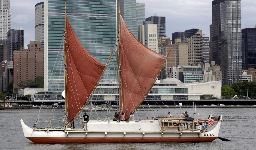 The traditional Polynesian voyaging canoe Hokulea, on an around-the-world journey guided only by nature, sails by the United Nations on New York's East River, during World Oceans Day on June 8, 2016.