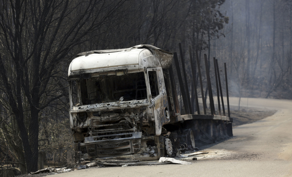 A burnt truck lies on a dirt road between Castanheira de Pera and Figueiro dos Vinhos in central Portugal on Sunday. Forest fires killed at least 61 people, many of them trapped in their cars as flames swept over a road.