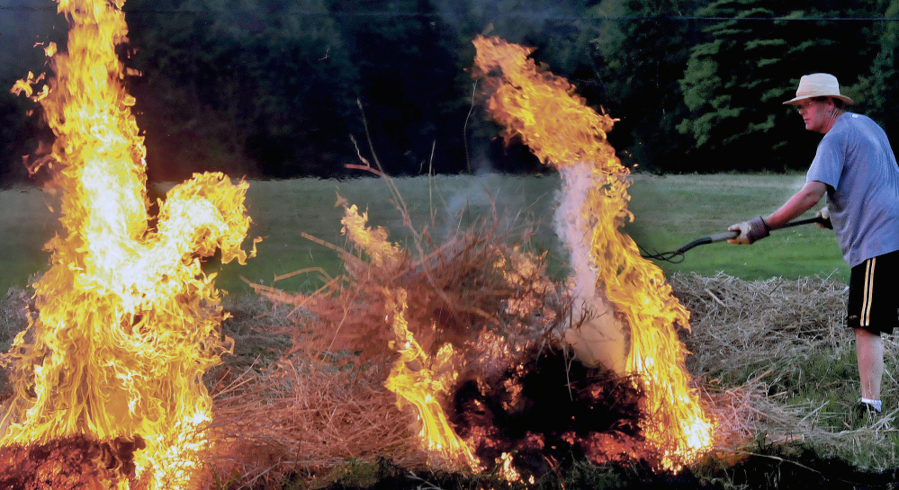 Peter Clifford throws a pitchfork full of burning brush to ignite another pile in August. A bill to allow municipalities to issue their own permits stalled in the Legislature.