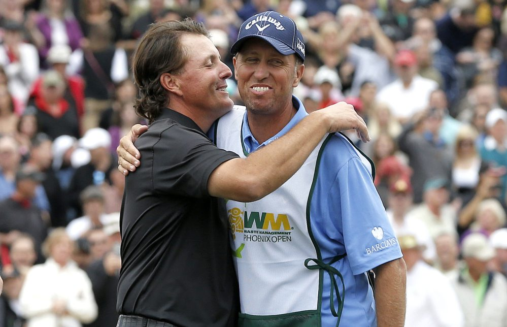 Phil Mickelson, left, hugs his caddie, Jim Mackay, after winning the Phoenix Open in 2013. Mickelson and Mackay have decided to part ways after 25 years of one of the PGA's most famous player-caddie relationships.