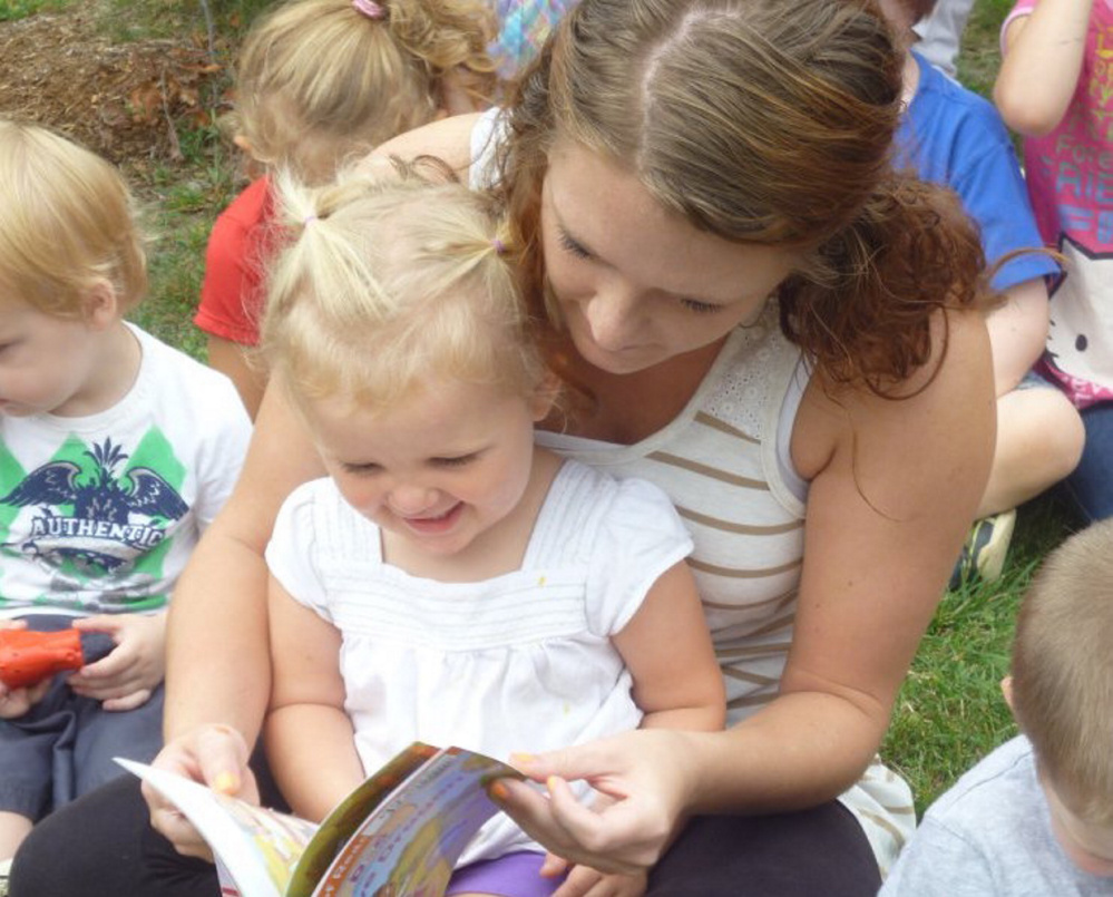 Charli Cote reads her new book with Educare Central Maine staff member Leeannza Delosh in 2015. Over 8,000 Maine children are eligible for Early Head Start services like those provided by Educare, but there are only 837 funded Early Head Start slots in the state.