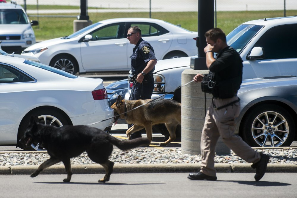 Police dogs search cars in a parking lot at Bishop International Airport on Wednesday morning in Flint, Mich. Officials evacuated the airport after an airport officer was stabbed in the neck.