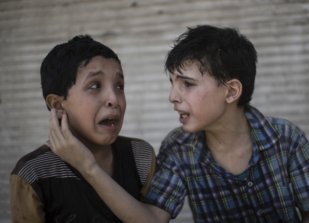 Cousins Zeid Ali, 12, left, and Hodayfa Ali, 11, comfort each other after their house was hit during fighting between Iraqi forces and the Islamic State in Mosul.