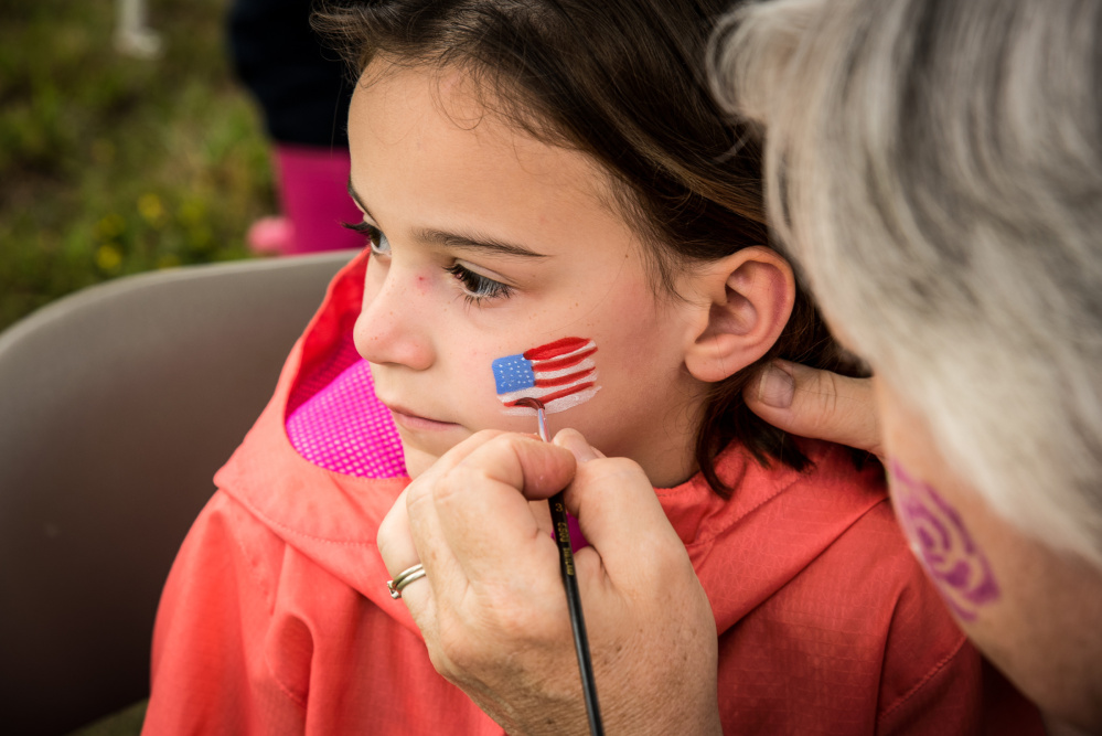 Vanessa Tyler, 6, of Augusta gets a flag painted on her face Saturday during Kennebec River Day at Mill Park in Augusta.