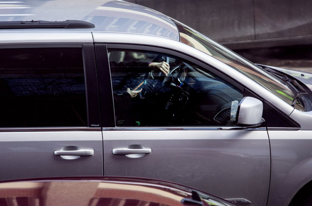 A motorist drives down Temple Street in Portland with one hand on the wheel and one hand on the phone. Researchers have found that hands-free devices are just as great a distraction for drivers as hand-held ones.