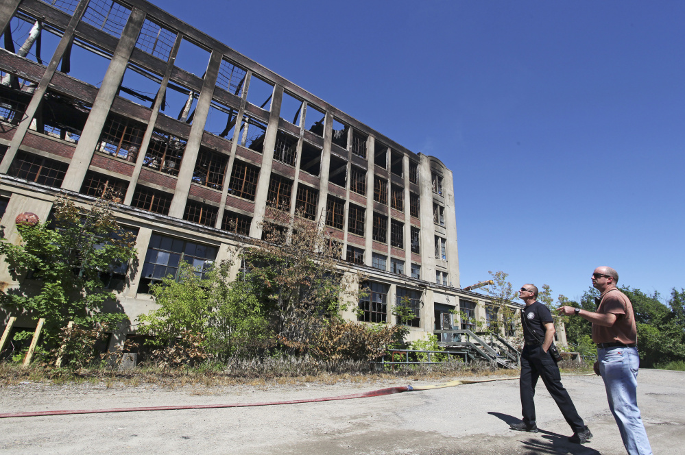 Sanford Fire Chief Steve Benotti and firefighter Todd Levesque survey the still-smoldering mill  building on Sunday. The city now plans to seek state and federal funding to help with the cleanup.