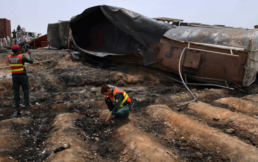 Pakistani rescue workers examine the site of an oil tanker explosion on a highway near Bahawalpur on Sunday.