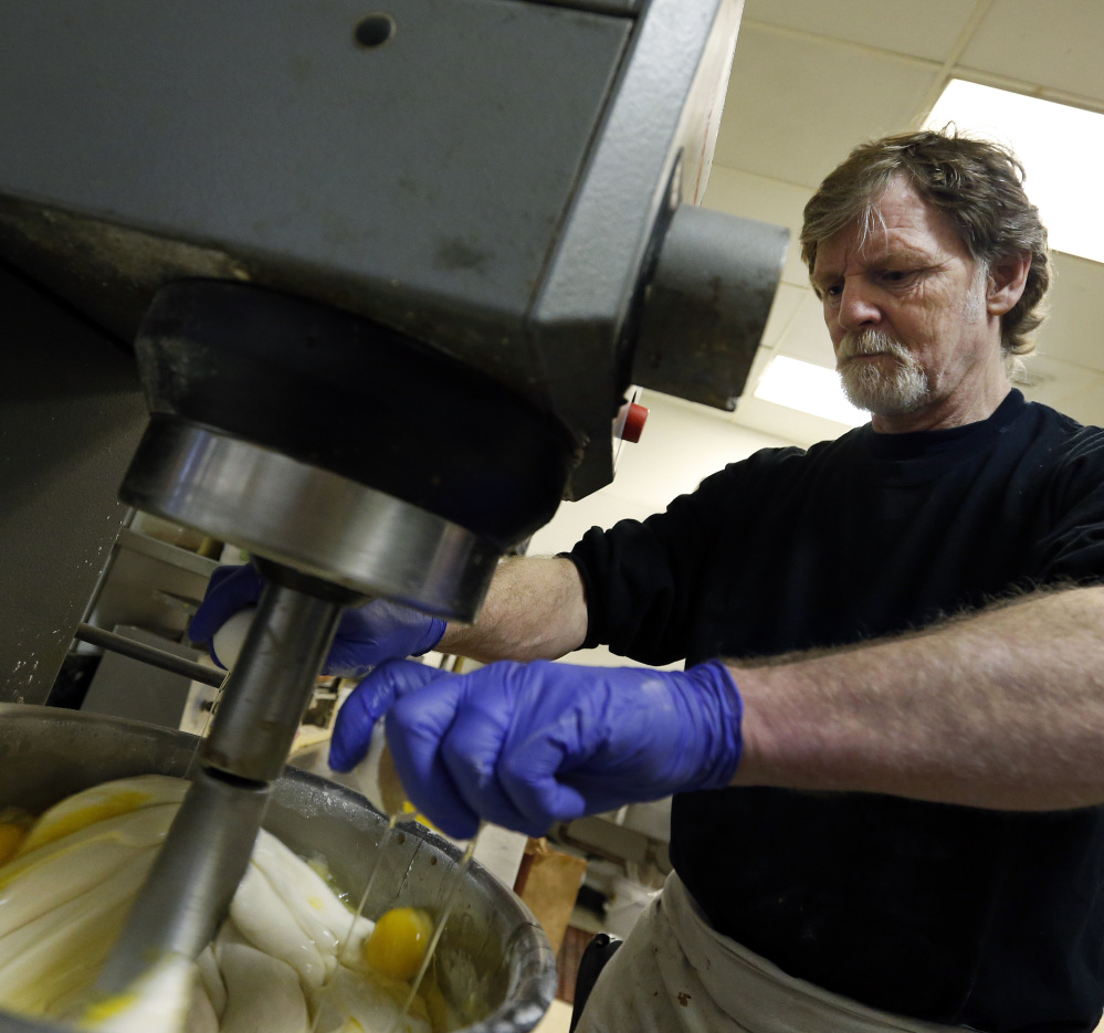 Masterpiece Cakeshop owner Jack Phillips cracks eggs into a cake batter mixer in his store in Lakewood, Colo. He refused to make a wedding cake for a gay couple.