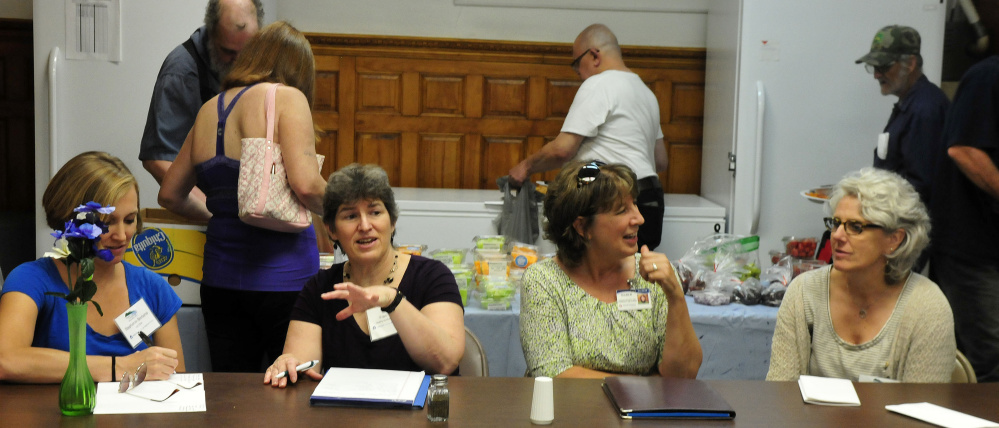 Officials with the EPA and other agencies held a meeting during lunch at the Sacred Heart Soup Kitchen in Waterville on Monday. The group is touring Waterville facilities that contribute to a healthy environment. As clients select donated food in back, Stephanie Bertaina, left, of the EPA, Fran Mullin of Healthy Northern Kennebec, Ellen Wells of Inland Hospital and Chris Beling of the EPA discuss issues.